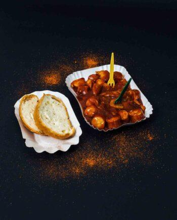Currywurst in Schale mit Pommespieksern