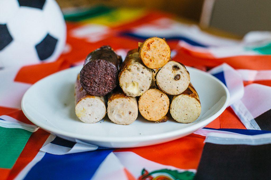 Acht verschiedene Grillwürste auf Teller mit Länderflaggen
